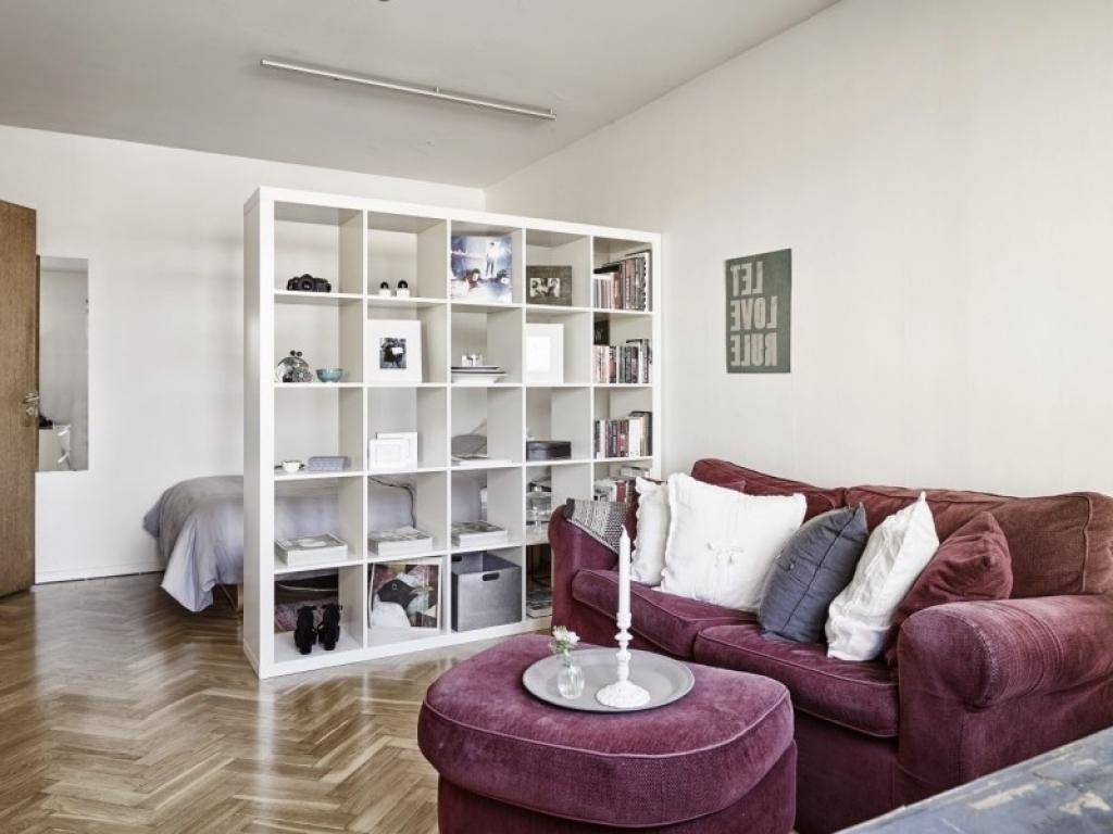 Спальное ложе за белым стеллажом в гостиной