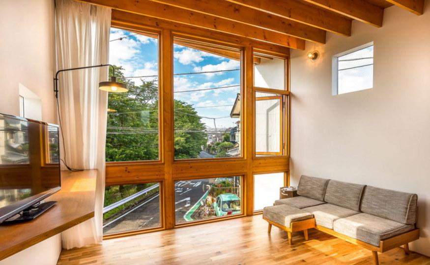 Узкие балки на потолке комнаты с большим окном
