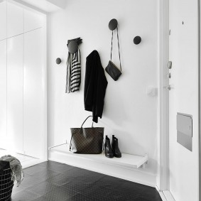 Одежда на крючках в белом коридоре