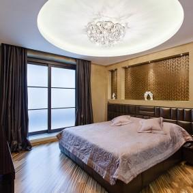 Круг с подсветкой над кроватью в спальне супругов