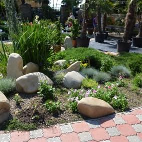 Каменистая клумба около дорожки из цементной плитки