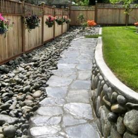 Мокрая поверхность дорожки из плоских камней