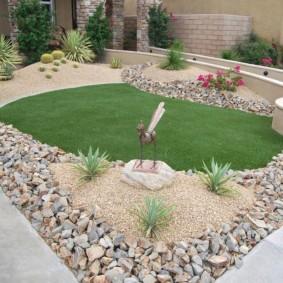 Зеленая лужайка в обрамлении камней среднего размера