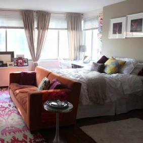 Просторная комната с диваном и кроватью