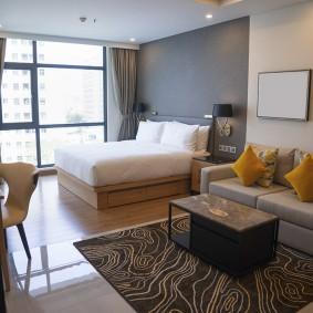 Двухспальная кровать в гостиной с панорамным окном