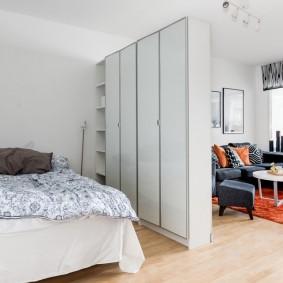 Узкие шкафы в роли разделителя пространства гостиной