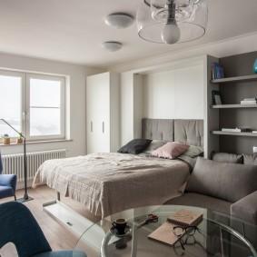 Серый диван в комнате без штор на окнах