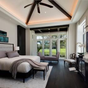 Темный пол в спальне с большим окном