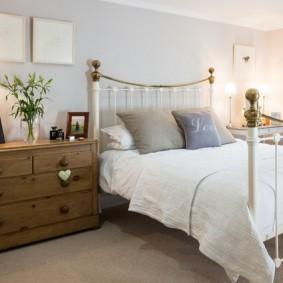 Деревянный комод около металлической кровати