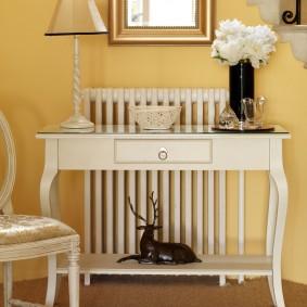 Белая мебель на фоне желтой стены прихожей