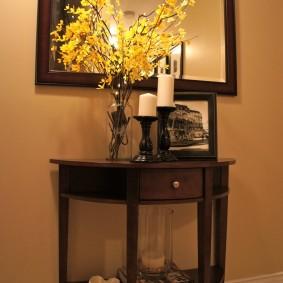 Ветки с желтыми листочками на столике перед зеркалом