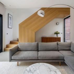 Серый диван в комнате с лестницей