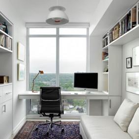 Письменный стол перед окном в узкой комнате