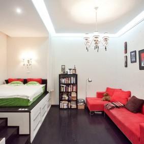 Красный диван в комнате с белыми стенами