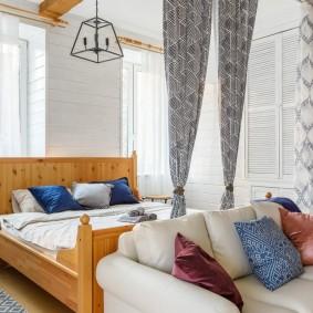 Деревянная кровать за спинкой дивана