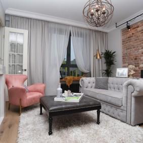 Розовое кресло в комнате с кирпичной стеной