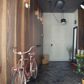 Велосипед на паркетном полу в коридоре