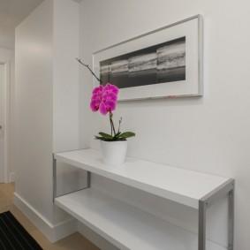 Цветущая орхидея на столике в прихожей