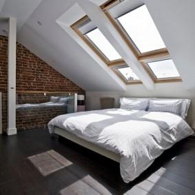 Широкая кровать под мансардными окнами