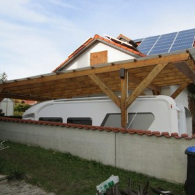 Высокие навес у дома с солнечными батареями на крыше