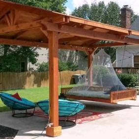 Кровать-качели под деревянным навесом