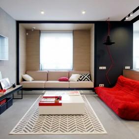 Красный диван в комнате городской квартиры