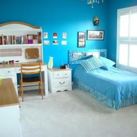 Узкая кровать в спальне с синими стенами