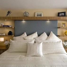 Белые подушки на кровати с серой спинкой