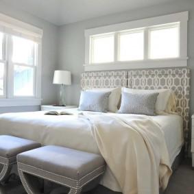 Банкетки серого цвета около кровати