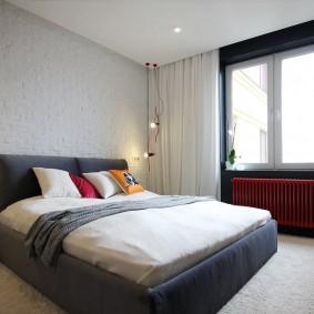 Красная батарея под окном в спальне