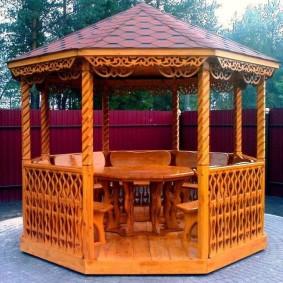 Деревянный стол внутри садовой беседки