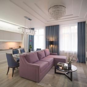 Сиреневый диван в роли разделителя пространства кухни-гостиной