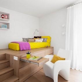 Желтый матрас на деревянном подиуме