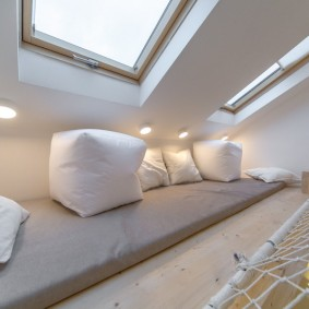 Белые подушки под мансардным окном