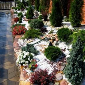 Первый снег на клумбе с хвойными растениями
