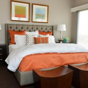Две картины над кровать с оранжевым покрывалом