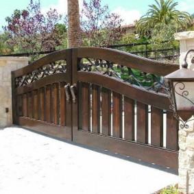 Садовый фонарь на заборе с воротами