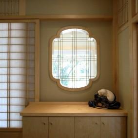 Тумбочка перед окном в прихожей комнате