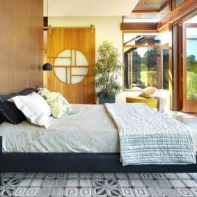 Широкая кровать в комнате с раздвижной стеной
