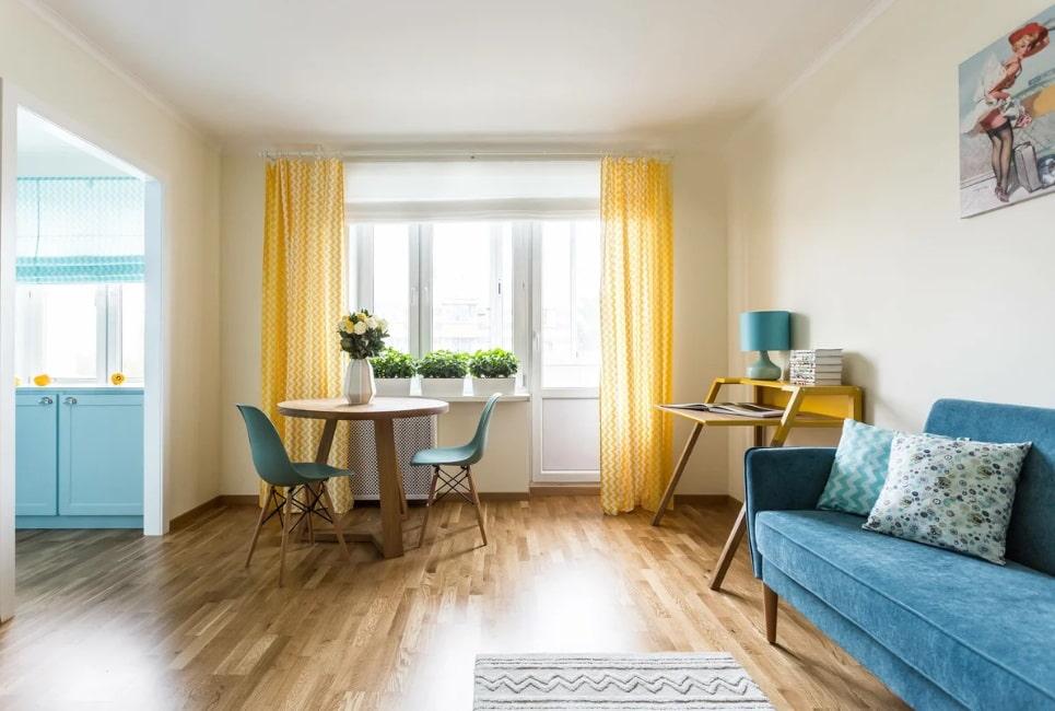 Интерьер гостиной комнаты после объединения с кухней