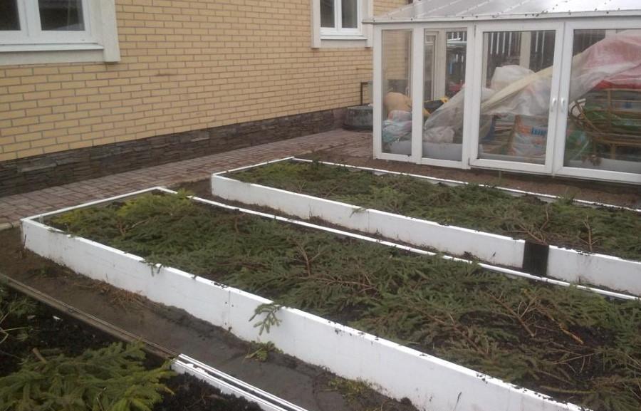 Белые грядки из ПВХ-подоконников перед кирпичным домом