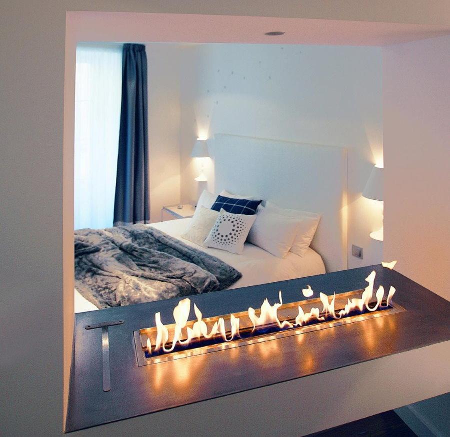 Ниша с камином и зеркалом в спальне небольшой площади