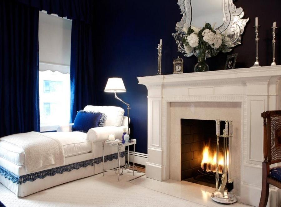 Синие стены в спальной комнате с камином