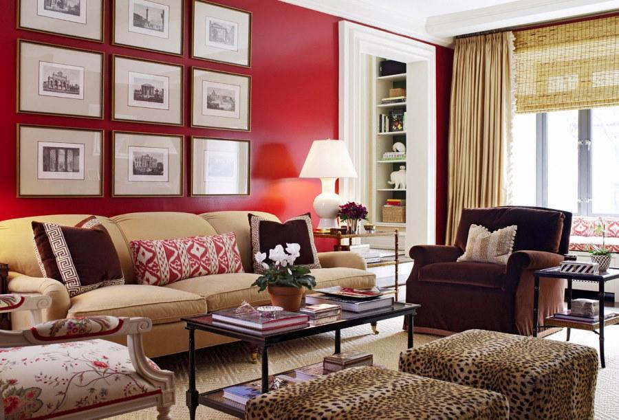 Красная стена в комнате с бежевым диваном