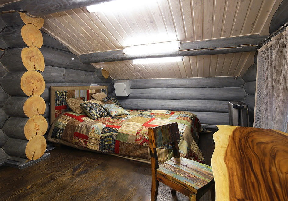 Уютная спальня в мансарде деревянного дома