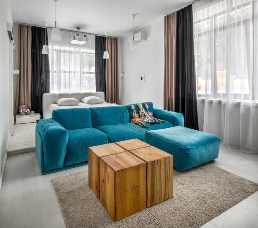 Размещение кровати за диваном в угловой гостиной