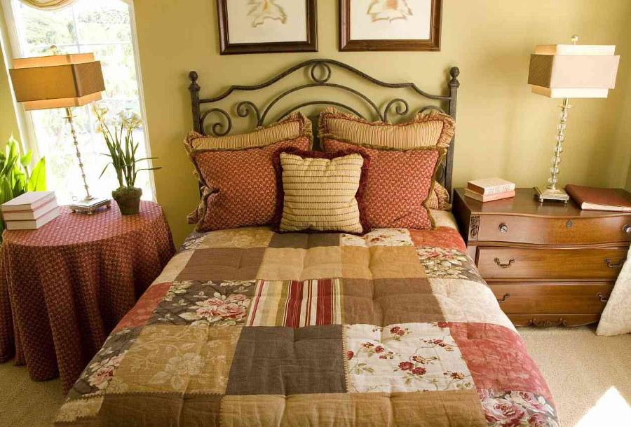 Настольные лампы около кровати в спальне стиля кантри