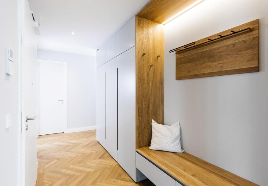 Деревянная вешалка на белой стене коридора