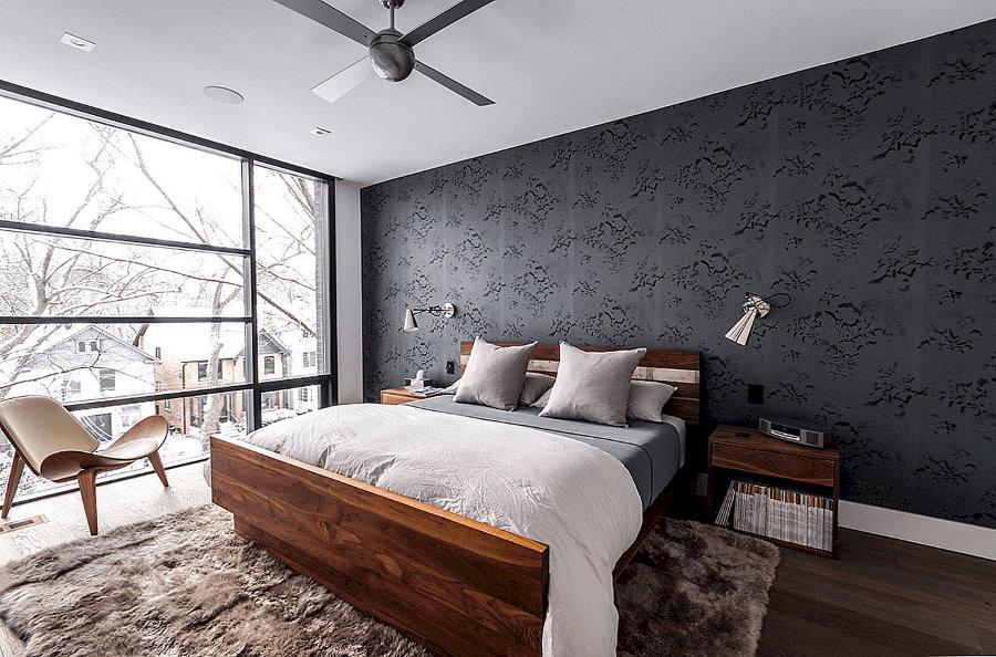 Деревянная кровать в спальне с серыми обоями