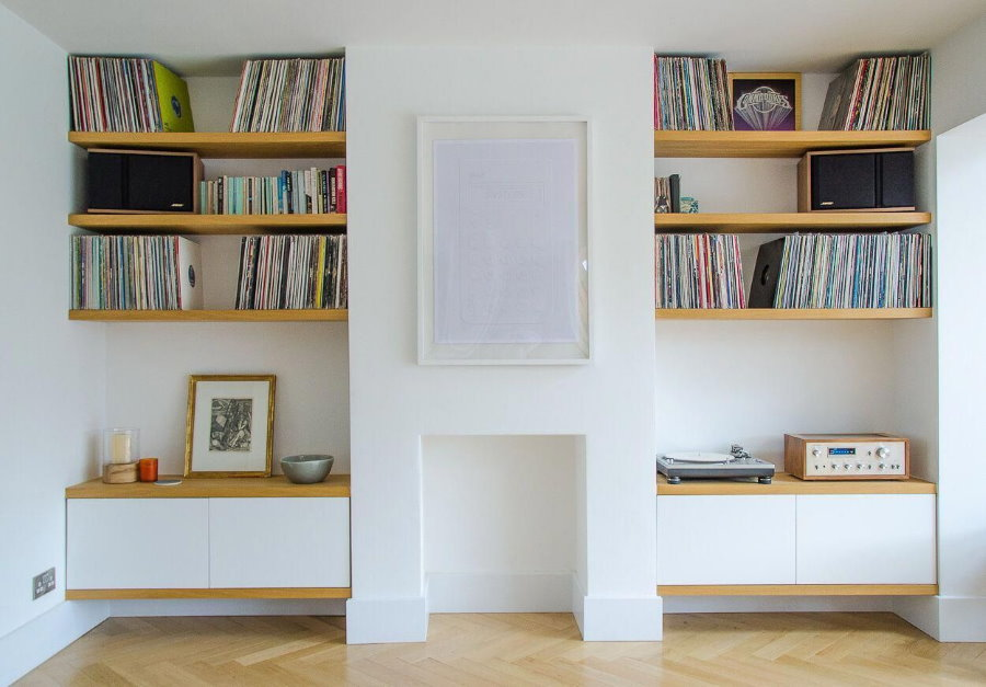 Книжные полки в нишах стены комнаты с белыми стенами